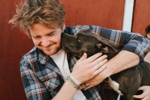 man hugging a dog
