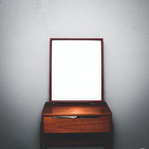 A wooden desk with a mirror