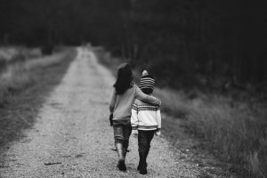 Two kids walking while embraced