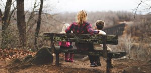 A single mom sitting on a bench with her two kids and talking about relocating as a single parent