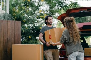 a man and a woman unpacking the car and carrying a moving box as they want to choose the best neighborhood.