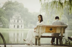 A couple sitting on a bench turning away from each other
