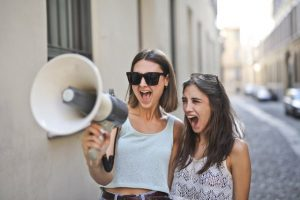 two girls on a megaphone want to break the news about moving