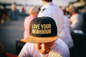 "A man with a ""love your neighbor"" hat"