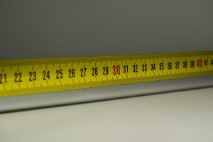 Picture of a measuring tape. Measure everything twice before you rearrange your furniture after moving