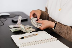 Picture of a woman counting money. Moving in as a couple requires smart budgeting