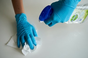 Person wearing blue gloves and wipes table