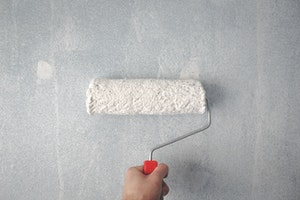 Person holding white paint roller on wall