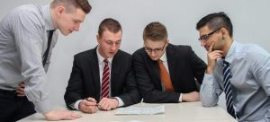Four man on a table looking into papers