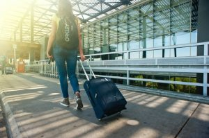 A woman is traveling carrying her luggage