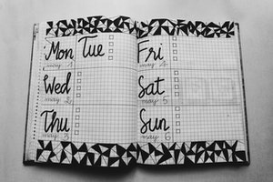 White and black weekly planer on gray surface