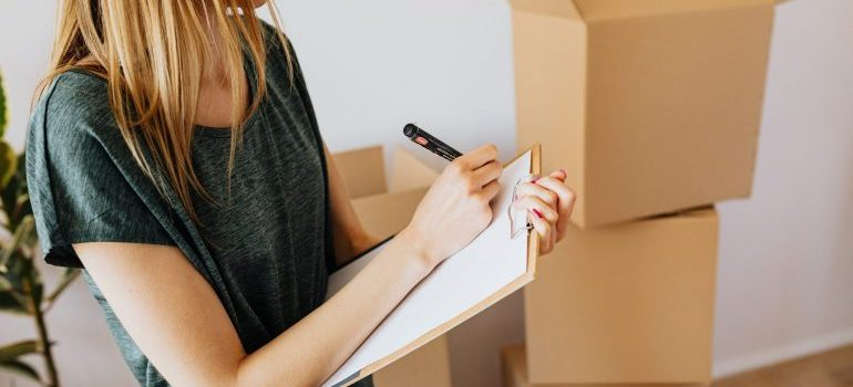 A packer with a checklist and cardboard boxes