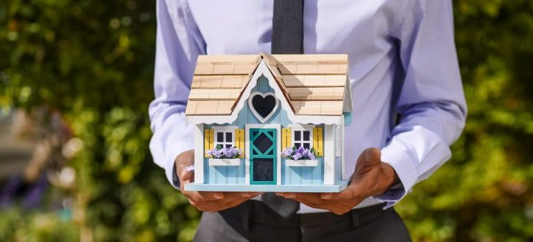 A person holding a model house