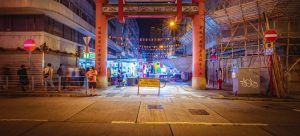 A traditional Chinese gate in the center of a lively city during night