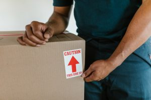 man holding a box with fragile sign