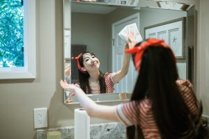 a girl cleaning a mirror