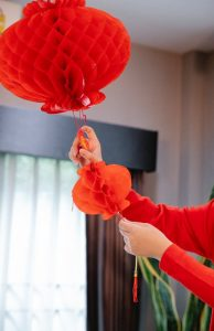 person fixing a red lantern